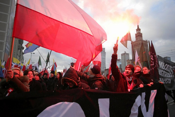 Protesters light flares and carry Polish flags during a rally, organised by far-right nationalist groups, to mark 99th anniversary of Polish independence in Warsaw